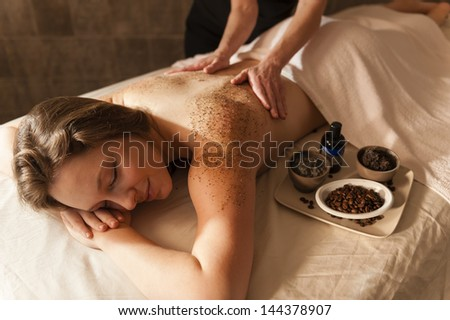 Beautiful young woman receiving a massage in a spa.
