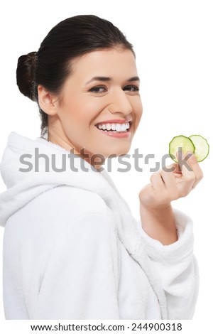 Beautiful young woman receiving facial mask of cucumber. - stock photo