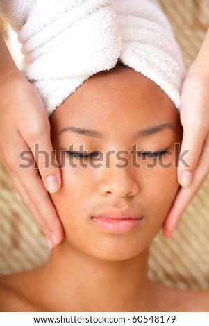 Beautiful young woman receiving facial massage - stock photo