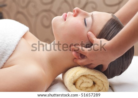 Beautiful young woman receiving head massage, shallow depth of field