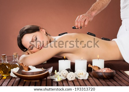 Beautiful young woman receiving hot stone therapy in spa