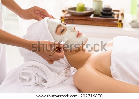 Beautiful young woman receiving white facial mask in the beauty salon - stock photo