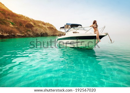 Beautiful young woman recreation on the boat a sunny summer day. Luxury vacation at sea. - stock photo