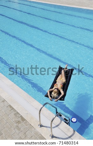 beautiful young woman relax and have fun at swimming pool - stock photo