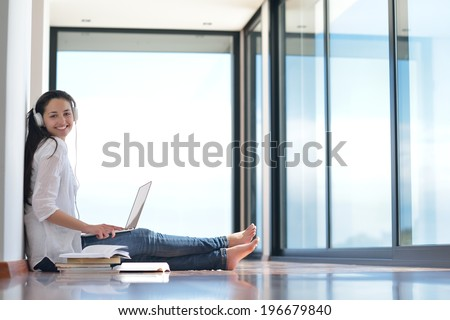 beautiful young woman relax and work on laptop computer while listening music on heaphones and read book at home - stock photo
