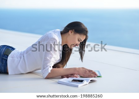 beautiful young woman relax and work on laptop computer while listening music on heaphones and read book at home