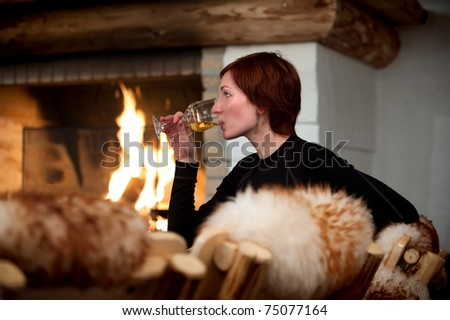beautiful young woman relaxing and drinking wine in a cozy house with fireplace - stock photo