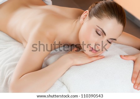 Beautiful young woman relaxing and lying at health spa club