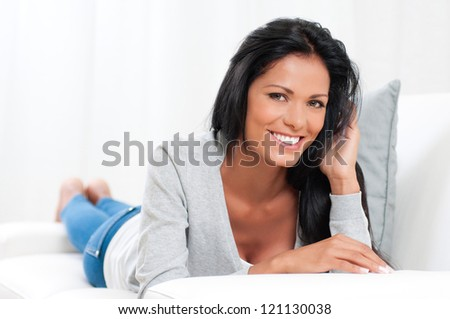 Beautiful young woman relaxing and lying on sofa at home - stock photo