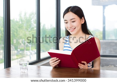 beautiful young woman relaxing and reading a book in a coffee shop - stock photo