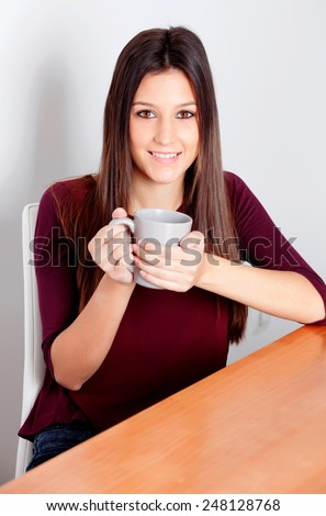 Beautiful young woman relaxing at home drinking tea - stock photo