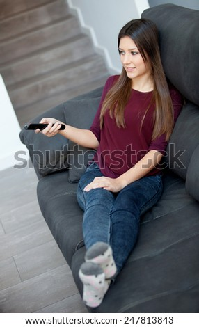 Beautiful young woman relaxing at home watching TV