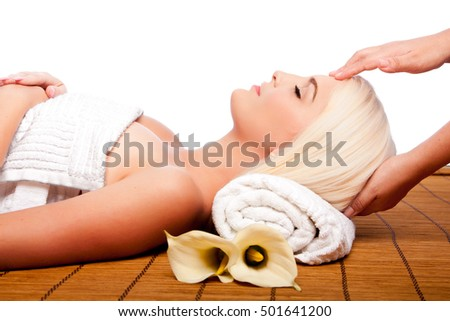 Beautiful young woman relaxing at spa getting therapeutic pampering forehead massage.
