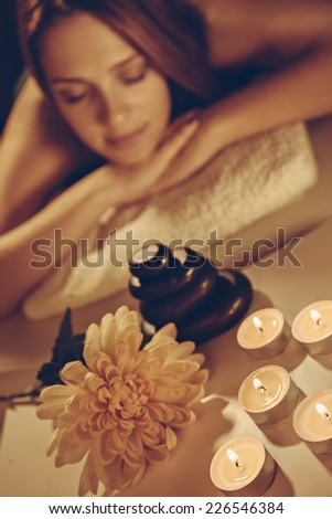 Beautiful Young Woman Relaxing At The Spa. Focus Is On Flower And Candles. - stock photo