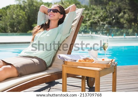 Beautiful young woman relaxing by swimming pool with breakfast on table - stock photo