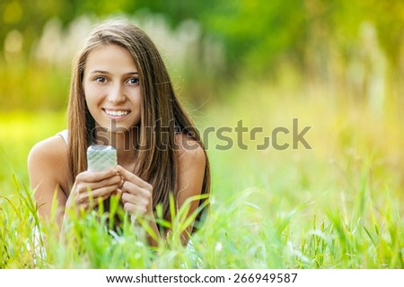 beautiful young woman relaxing grass lying with phone
