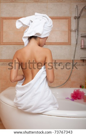 Beautiful young woman relaxing in a bathroom. - stock photo
