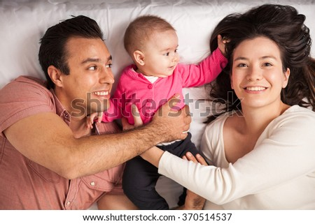 Beautiful young woman relaxing in a bed at home with her husband and her baby daughter