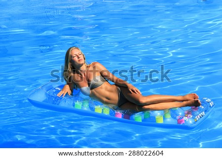 Beautiful young woman relaxing in a swimming pool in Greece