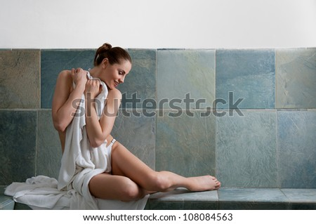 Beautiful young woman relaxing in a Turkish bath at spa