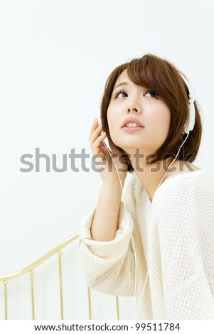 Beautiful young woman relaxing in bedroom. Portrait of asian woman. - stock photo
