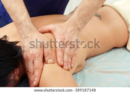 Beautiful young woman relaxing in spa with back massage