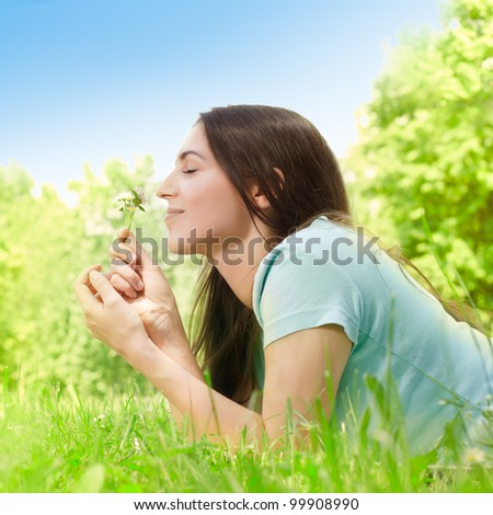 Beautiful young woman relaxing in the park at sunny spring day.