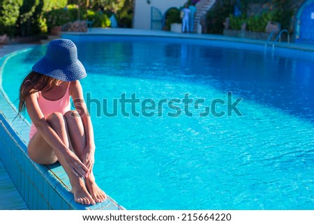 Beautiful young woman relaxing near the swimming pool - stock photo