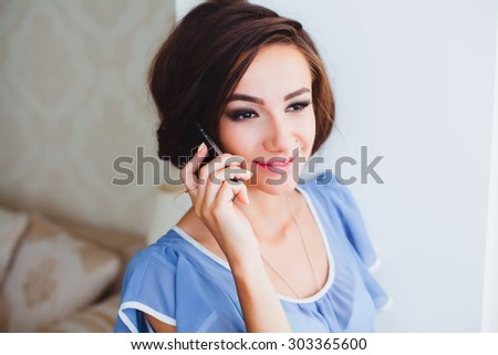 Beautiful young woman relaxing on a bed at home, using a smartphone to network on line, interior. Home living and technology lifestyle. Girl using a touch screen mobile phone in her bedroom, smiling.  - stock photo