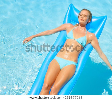 Beautiful young woman relaxing on a  mattress in clear blue water - stock photo