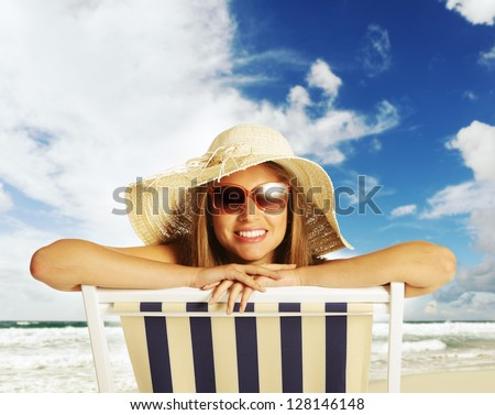 Beautiful young woman relaxing on beach chair - stock photo