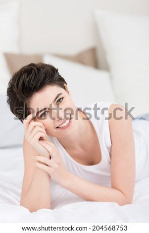 Beautiful young woman relaxing on her bed lying on her stomach looking at the camera with a happy beaming smile