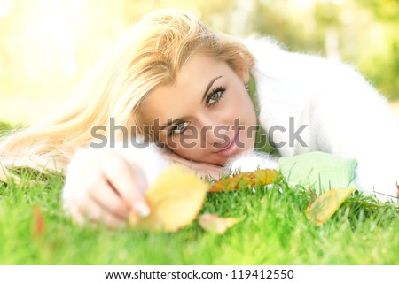 Beautiful young woman relaxing on the grass. - stock photo