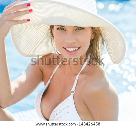 Beautiful young woman relaxing on the poolside - stock photo