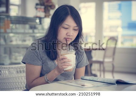 Beautiful young woman relaxing with coffee and a magazine sitting at the cafe, process color - stock photo