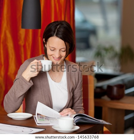 Beautiful young woman relaxing with coffee and a magazine sitting at the dining room table in her house - stock photo