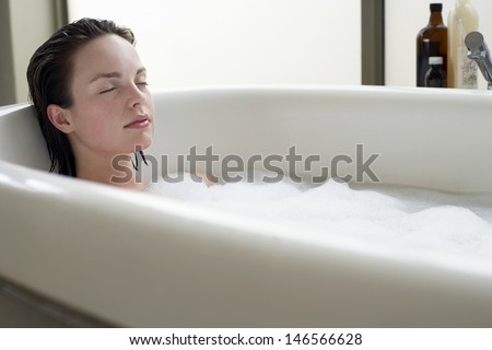 Beautiful young woman relaxing with eyes closed in bathtub - stock photo