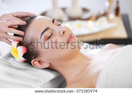 Beautiful young woman relaxing with face massage at beauty spa - stock photo