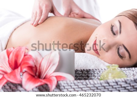 Beautiful young woman relaxing with hand massage at beauty spa.