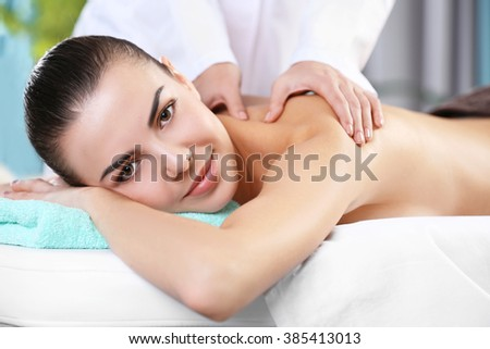 Beautiful young woman relaxing with hand massage at beauty spa, closeup