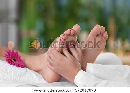 Beautiful young woman relaxing with leg massage at beauty spa - stock photo