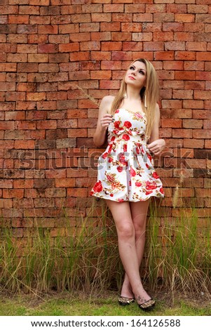 Beautiful Young Woman Relaxing With Old Brick Wall - stock photo