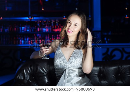 beautiful young woman, rest on Leather sofa and drinks beverage