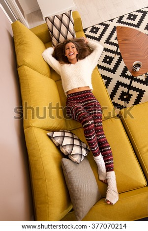 Beautiful young woman resting and enjoying at living room. She is laying at sofa with her hands behind head. Top view. - stock photo