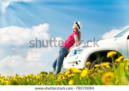 Beautiful young woman resting at bonnet of her car at flower field with blue cloudy sky in background - stock photo