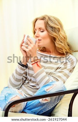 Beautiful young woman resting at home in a cozy armchair with a cup of tea. Interior. - stock photo