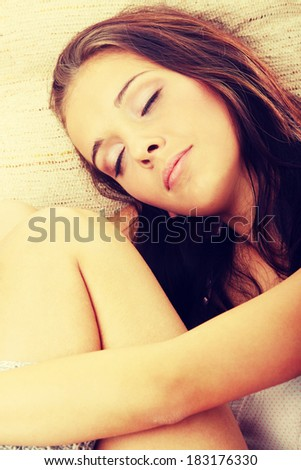 Beautiful young woman resting in armchair.