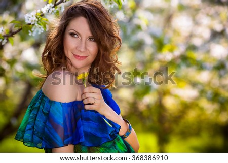 Beautiful young woman resting in spring garden - stock photo
