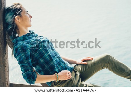 Beautiful young woman resting on coast and enjoying view of sea