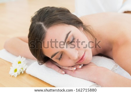 Beautiful young woman resting with eyes closed on towel at beauty spa